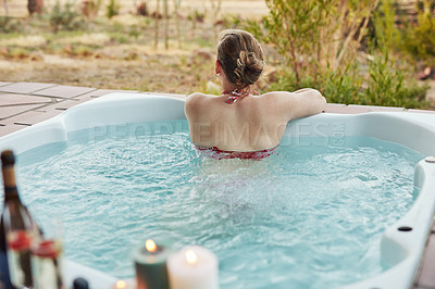 Buy stock photo Cropped shot of unrecognizable woman sitting in a jacuzzi alone during a relaxing day at a spa