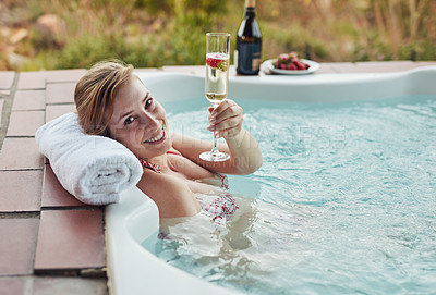 Buy stock photo Cropped portrait of an attractive young woman sitting in a jacuzzi and enjoying a glass of champagne at a spa