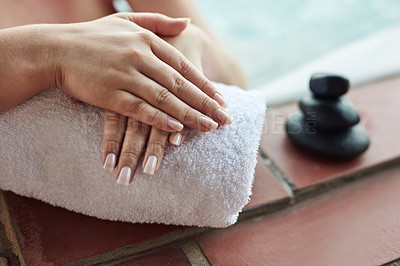 Buy stock photo Cropped shot of an unrecognizable woman placing her hands on a towel while at the spa during the day