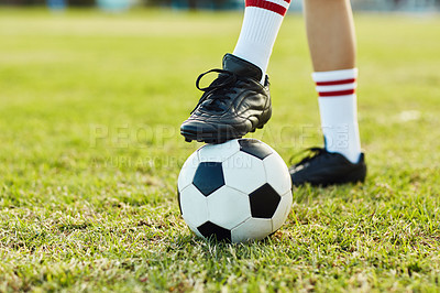Buy stock photo Cropped shot of an unrecognizable female soccer player posing with a soccer ball on the field