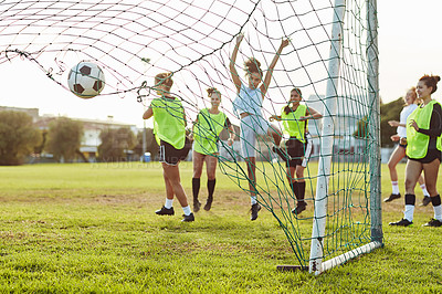 Buy stock photo Full length shot of a young sportswoman celebrating after scoring a goal for her team during a soccer match outdoors