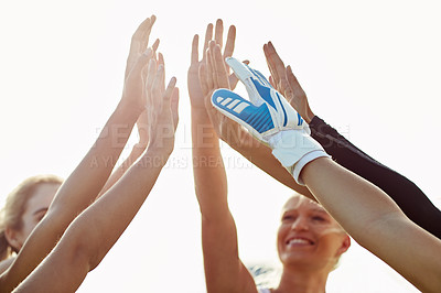 Buy stock photo Cropped shot of a team of female soccer players joining hands together for a high five outdoors