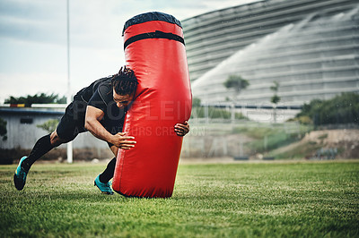 Buy stock photo Full length shot of a handsome young rugby player working out with a tackle bag on the playing field