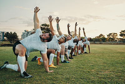 Buy stock photo Full length shot of a group of young rugby players training on the field during the day