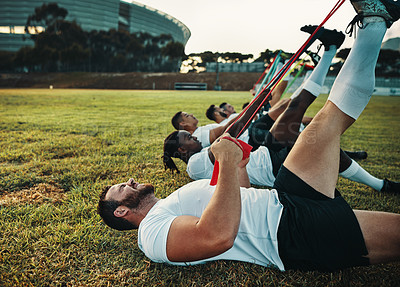 Buy stock photo Cropped shot of a group of young rugby players training with bands on the field during the day