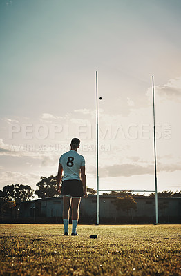 Buy stock photo Rearview shot of a handsome young rugby player kick  training on the field during the day