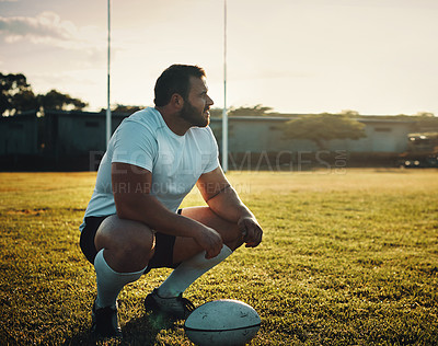 Buy stock photo Full length shot of a handsome young rugby player crouching on the field during the day