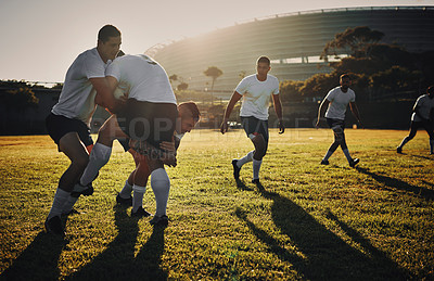 Buy stock photo Full length shot of a group of rugby players tackling during a training session on the field