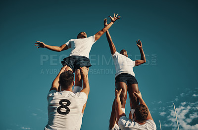 Buy stock photo Low angle shot of two handsome young rugby players catching the ball during a lineout on the field