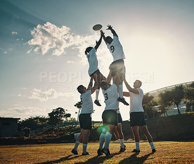 Buy stock photo Full length shot of two handsome young rugby players catching the ball during a lineout on the field