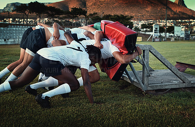 Buy stock photo Cropped shot of a group of young rugby players training with tackle bags on the field during the day