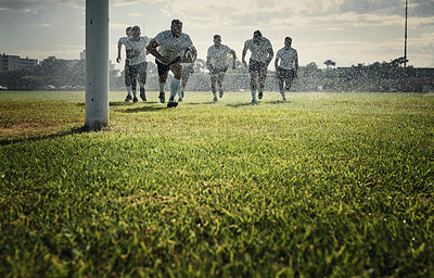 Buy stock photo Full length shot of a handsome young rugby player on his way to score a try while training on a rainy day