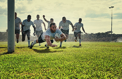 Buy stock photo Full length shot of a handsome young rugby player scoring a try while training on a rainy day