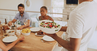 Buy stock photo Cropped shot of a man serving salad during a get together with friends at home