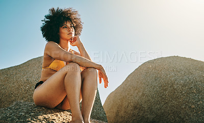 Buy stock photo Cropped shot of an attractive young woman sitting on a rock and posing during a day out at the beach