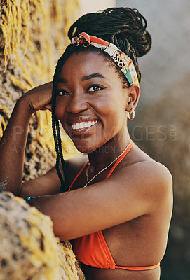 Buy stock photo Cropped portrait of an attractive young woman standing against a rock and posing during a day out at the beach