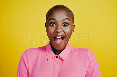 Buy stock photo Portrait of an attractive young woman looking cheerful and surprised in studio against a yellow background