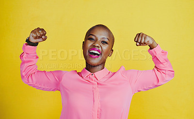 Buy stock photo Portrait of an attractive young woman flexing her biceps against a yellow background