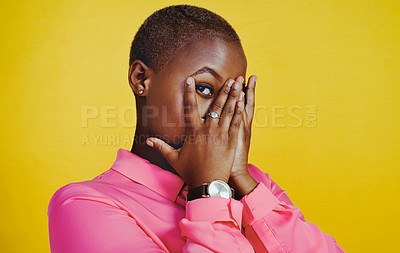 Buy stock photo Portrait of an attractive young woman covering her face with her hands against a yellow background