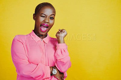 Buy stock photo Cropped shot of an attractive and cheerful young woman winking in studio against a yellow background