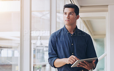 Buy stock photo Shot of a young businessman looking thoughtful while using a digital tablet in an office