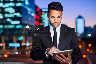 Buy stock photo Cropped shot of a handsome young businessman using a digital tablet outdoors in the evening with the cityscape in the background