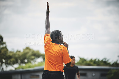 Buy stock photo Cropped shot of a referee blowing his whistle while lifting his hand up in the middle of a rugby match on a field during the day