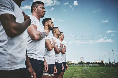 Buy stock photo Cropped shot of a team of confident young rugby players standing at attention singing their anthem outside on a field before a rugby match