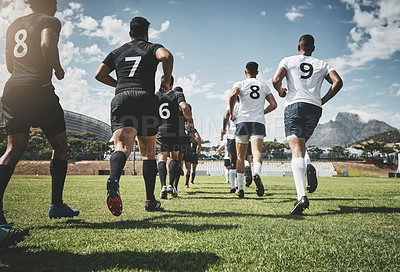 Buy stock photo Low angle shot of two focused young rugby teams jogging up onto the field together to start the match outside during the day