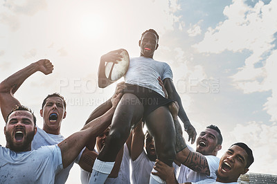 Buy stock photo Portrait of a group of cheerful young rugby players celebrating their win by lifting one of their teammates