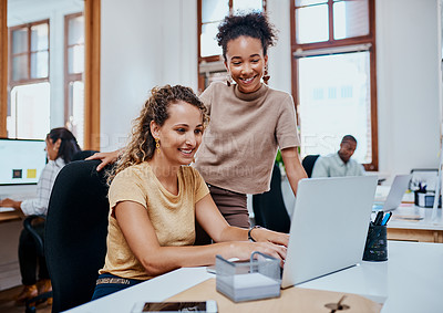 Buy stock photo Shot of two young businesswomen using a laptop together in a modern office