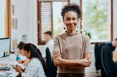 Buy stock photo Portrait of a confident young businesswoman working in a modern office with her team in the background