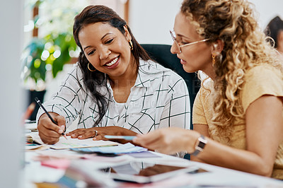 Buy stock photo Shot of two young businesswomen working together on a task in a modern office