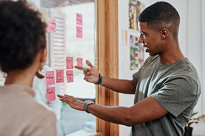 Buy stock photo Shot of a young young businessman and businesswoman having a brainstorming session in a modern office