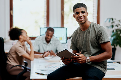 Buy stock photo Shot of a young businessman using a digital tablet during a meeting in a modern office