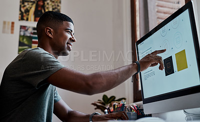 Buy stock photo Shot of a young businessman using a computer in a modern office