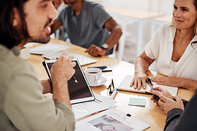 Buy stock photo Shot of a group of businesspeople using a digital tablet during a meeting in an office