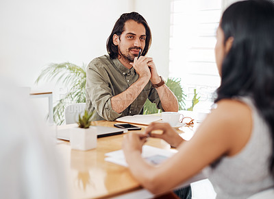 Buy stock photo Shot of a young businessman having a meeting with his colleague in an office