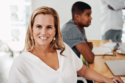 Buy stock photo Portrait of a mature businesswoman sitting in an office with her colleagues in the background