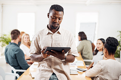 Buy stock photo Shot of a young businessman using a digital tablet in an office with his colleagues in the background