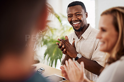 Buy stock photo Shot of a young businessman applauding during a meeting in an office
