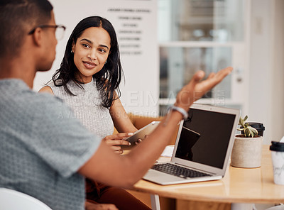 Buy stock photo Shot of a young businesswoman using a digital tablet while having a discussion with a colleague in an office
