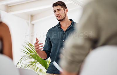 Buy stock photo Shot of a young businessman speaking at a conference