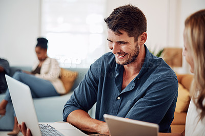 Buy stock photo Cropped shot of a handsome young businessman sitting with a colleague and using technology in the office