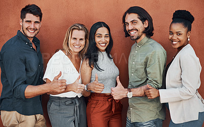 Buy stock photo Cropped portrait of a diverse group of businesspeople standing and making a thumbs up gesture against a wall outside