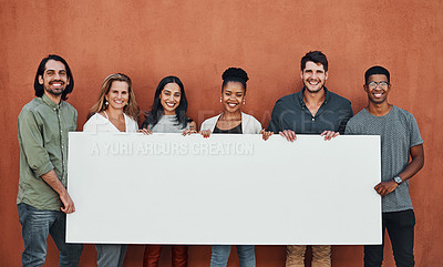 Buy stock photo Cropped portrait of a diverse group of businesspeople standing together and holding a sign while outside