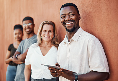 Buy stock photo Cropped portrait of a handsome young businessman standing with his colleagues outside and using a tablet