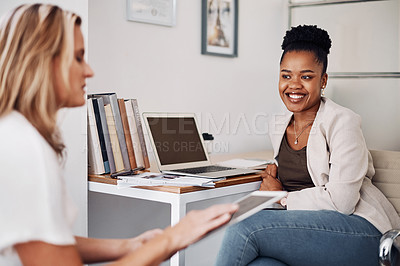 Buy stock photo Cropped shot of two attractive young businesswoman sitting together and having a discussion in the office