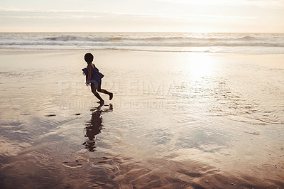 Buy stock photo Shot of an adorable little girl having fun on the beach at sunset