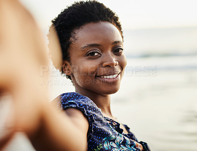 Buy stock photo Shot of a happy young woman taking selfies at the beach